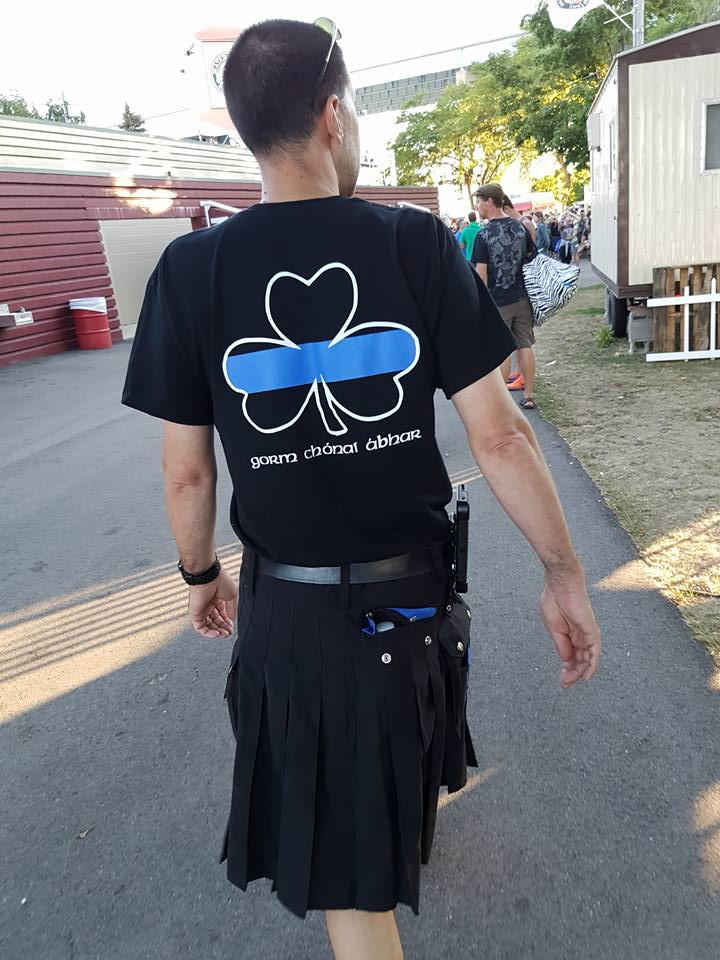 "View of a man from the back The man is wearing a black ""Utili-kilt"" and a black T-shirt featuring the ""Blue Lives Matter"" logo inside a shamrock, with the Irish words ""Gorm Chónaí Ábhar"" below the shamrock. Photo taken by Karen Reshkin at the 2016 Milwaukee Irish Fest and is used with her permission. Visit her website at www.acleversheep.net."